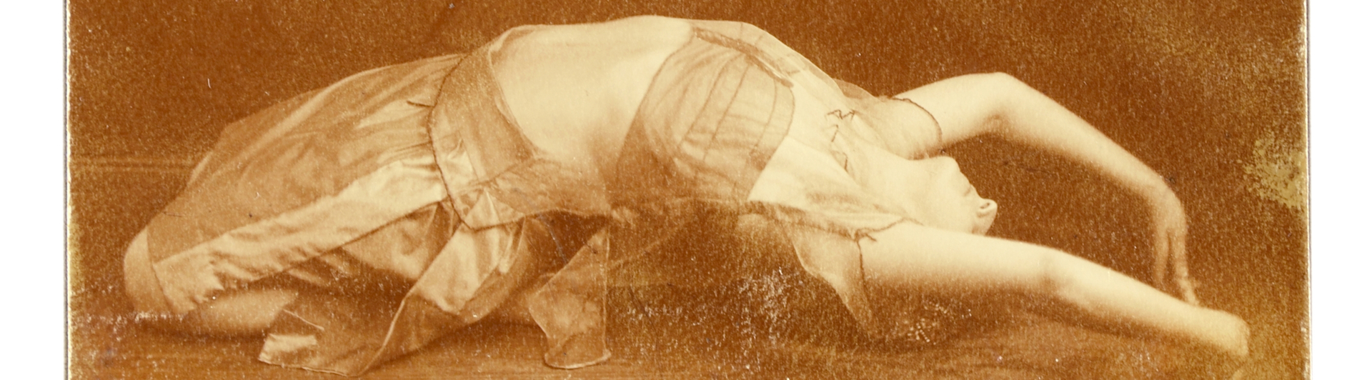 Old photographie showing a woman lying on the floor during a dance performance