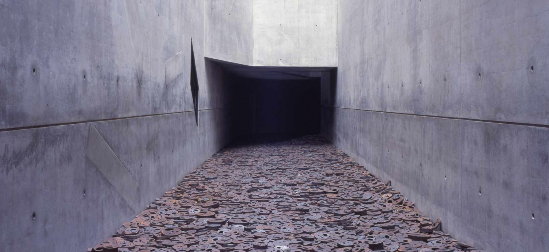 Ein Gang mit kahlen Betonwänden, der sich im Dunkeln verliert. Der Boden ist übersät mit dicken Metallscheiben, in die Gesichter mit aufgrissenen Mündern gesägt wurden.