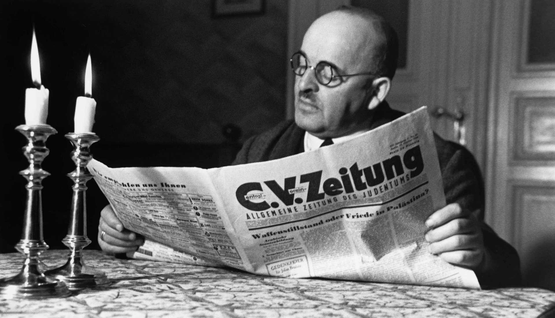 Black and white photo by Herbert Sonnenfeld: A man sitting at a table with two burning Shabbat candles and reading the C.V. newspaper