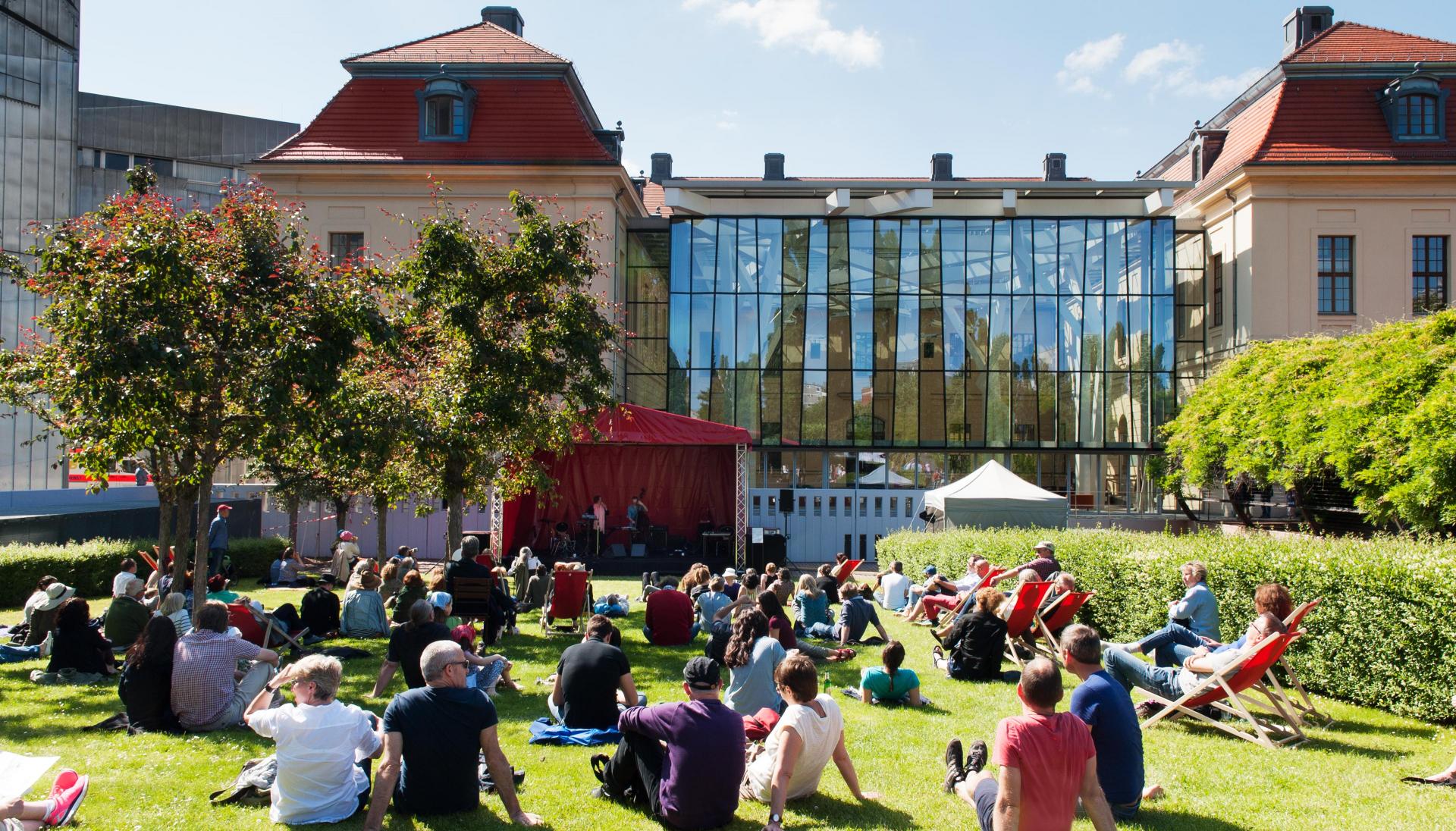 Foto vom Sommerfest im Garten des Museums. Besucher*innen sitzen in der Sonne auf dem Rasen und schauen in Richtung einer kleinen Bühne.