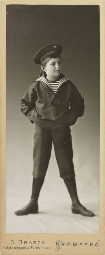 Schwarz-weiß-Foto: Junge im Matrosenanzug, breitbeinig stehend, die Arme in die Hüfte gestemmt, Atelieraufnahme
