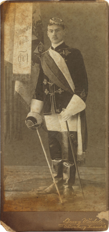 Black-and-white photograph: student in full fraternity regalia with a fencing foil, fraternity flag in the background