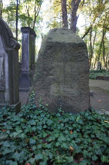 Farbfoto: Grabstein mit stark verwitterter Inschrift, Efeu berankt, im Hintergrund weitere Gräber