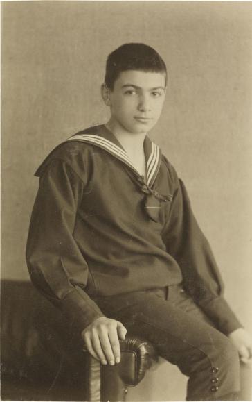 Schwarz-weiß-Foto: Sitzender Junge, Atelieraufnahme
