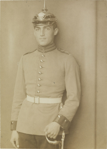 Black-and-white photograph: Young man in soldier's uniform with white belt, spiked helmet, and sword, studio portrait