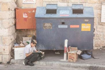 Ein Junge sitzt lesend vor einem Container am Straßenrand