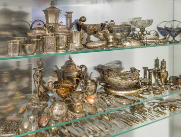 Glasvitrine voller Geschirr, Besteck und sonstiger Gegenstände aus Silber