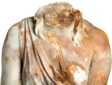 Weibliche Statue mit Rostspuren, der der Kopf fehlt