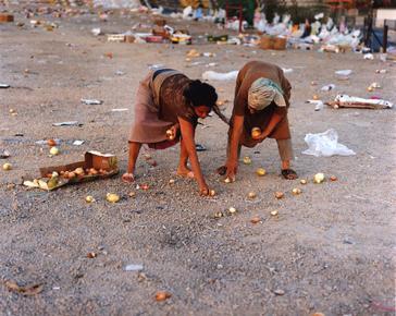 Künstlerisch inszeniertes Foto: Zwei weibliche Figuren sammeln übriggebliebene Zwiebeln vom Boden auf