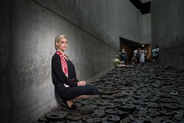 Eine junge Frau sitzt im Memory Void des Jüdischen Museums Berlin