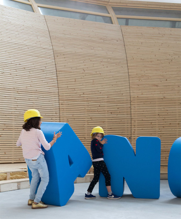 Children with construction helmets play with large letters of the lettering ANOHA