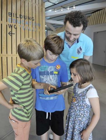 Drei Kinder und ein Mann schauen auf ein iPad