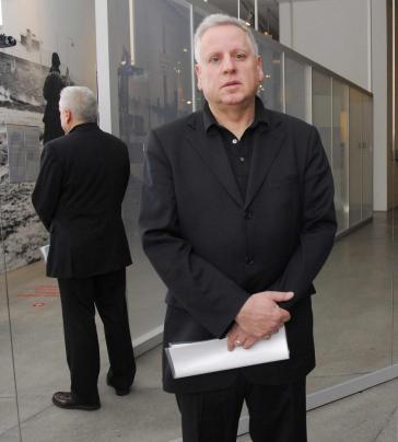 Stehender Mann in schwarzem Anzug vor einer verspiegelten Glasfläche, seine Körperrückseite ist als Spiegelbild zu sehen