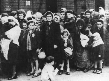 Schwarz-weiß Fotografie mit zahlreichen Personen unterschiedlichen Alters, den Judenstern tragend und vor einem Zug-Waggon stehend
