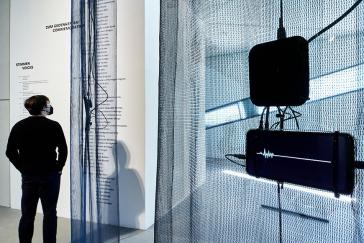 Raumansicht der Ausstellung mit Besucher, im Vordergrund ein Bildschirm mit einer Stimmwelle