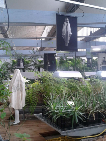 Plateau plant beds inside a large hall, in between them mannequins wearing fashion designs, and above them large-scale photographs