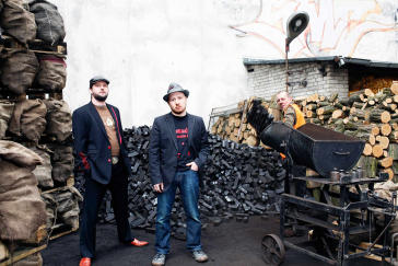 Three band members in front of a backdrop of firewood and coal