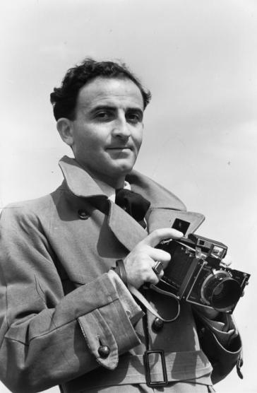 Schwarz-Weiß-Fotografie eines Mannes, der eine Kamera hält