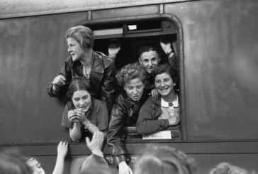 Schwarz-Weiß-Fotografie jugendlicher Jungen und Mädchen, die sich lachend aus einem Zugfenster lehnen.