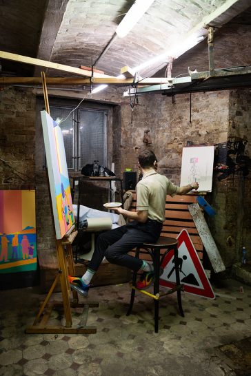 Photography of a person in front of an easel in a basement room, in the background there is a construction site sign on the floor