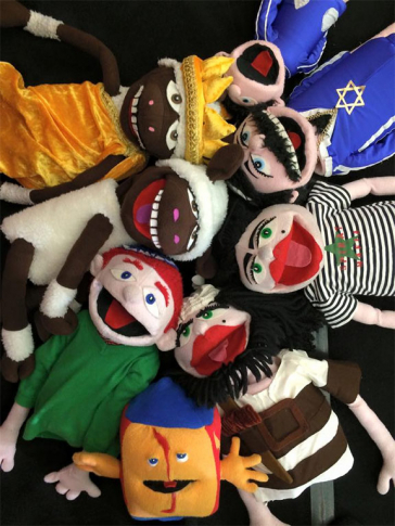 Eight colorful, mouth-moving hand puppets lying in a circle with their heads to the center, laughing at the onlookers.