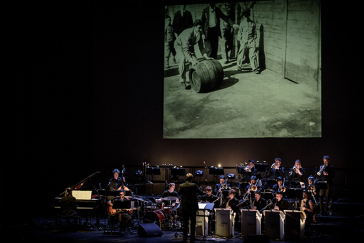 Photography: an orchestra playing underneath a screen showing a film