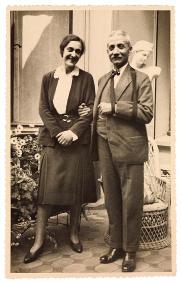 Schwarz-weiß-Fotografie zweier Menschen auf dem Vorplatz eines Hauses mit Blumen, Statue und Korbstuhl im Hintergrund