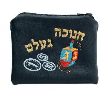 """Ein schwarzer Geldbeutel, auf den ein Dreidel, Münzen und in hebräischen Buchstaben das jiddische Wort """"Chanukka-Gelt"""" gestickt ist."""