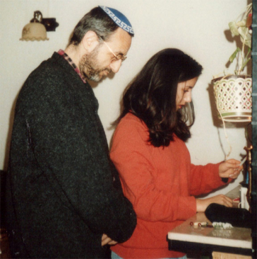 A young woman holding a candle on a candlestick; next to her, a man with a kippah.