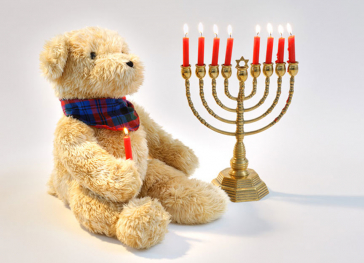 A teddybear holding a burning candle sits alongside an eight-branched lampstand