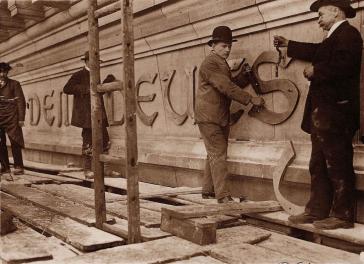 Handwerker mit Werkzeug bringen einen Schriftzug an einer Fassade an