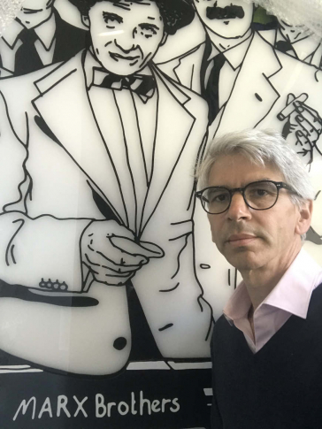 Portrait of Michael Dorrmann in front of a bust of the Marx Brothers