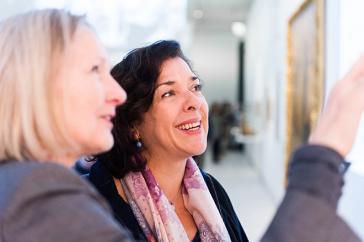 Auf dem Farbfoto deutet im Vordergrund Margret Kampmeyer auf ein Objekt außerhalb des Bildausschnitts. Elena Bashkirova betrachtet das Bild lachend.