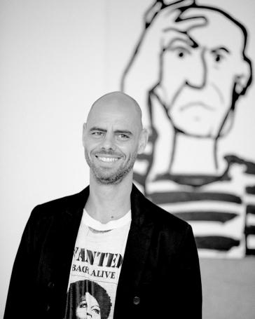 Schwarz-Weiss-Porträt von Eran Shakine vor einer seiner Zeichnungen