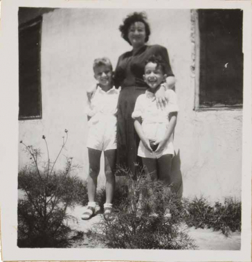 In black and white photography Leonie puts her hands on the shoulders of the children. They are dressed in white shorts and shirts, while Leonie wears a dark dress. In the background a house wall can be seen.