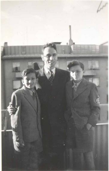 Auf dem Schwarz-Weiß-Foto steht Rolf Rothschild in der Mitte und hat seine Arme um die beiden Jungen gelegt. Alle tragen Anzug.
