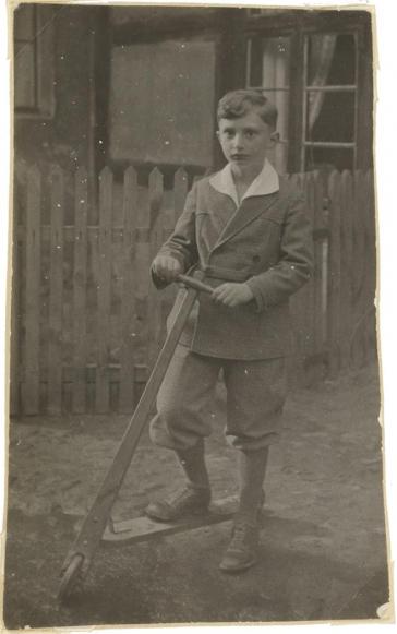 Fotografie Walter Frankensteins als Kind in feiner Kleidung und mit Roller vor einem Zaun stehend