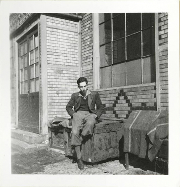 A young man sits in front of a house (black and white photo)