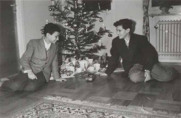 In the black-and-white photo, the two boys are sitting in front of a Christmas tree, smiling at the gifts that are strewn beneath it.