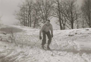 In the black-and-white photo, Walter is skiing up a small slope.