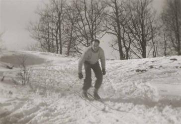 Auf dem Schwarz-Weiß-Foto fährt Walter auf Skiern einen kleinen Abhang hinab.