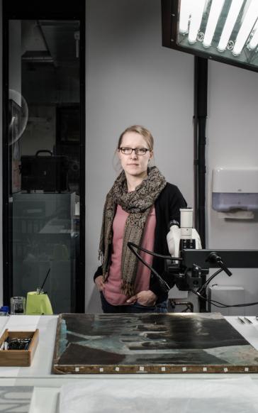 Eine junge Frau steht an einem Arbeitstisch in einem Atelier, vor ihr liegt ein altes Ölgemälde.