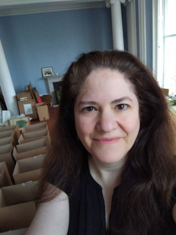 Selfie of Michal S. Friedlander in a room with boxes on the floor and blue wall paint