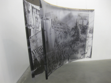 Installation of two black and white photographs, framed and mounted one behind the other on documents. The photos show the Jewish Agency Bombing (1948) and the  Destruction of the Moroccan Residential District by the Israeli Government (1967)