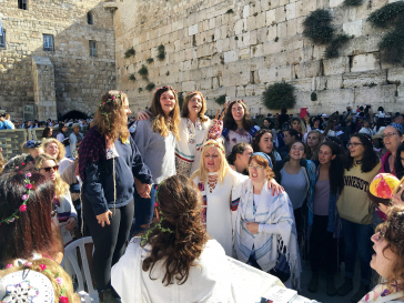 Singing women at the Wailing Wall, partly with wreaths of flowers and prayer shawls