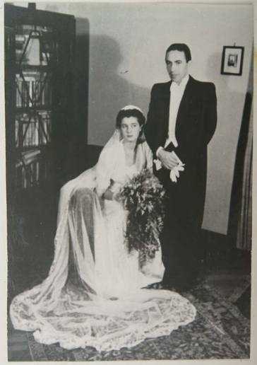 Black-and-white photo of a bridal couple. The bride is seated with the groom standing behind her. A cabinet is visible to the left in what appears to be a living room.