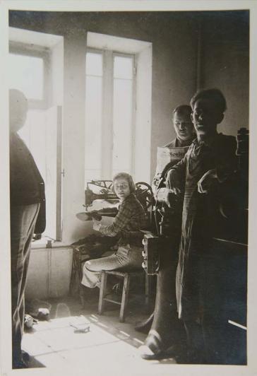 Schwarz-Weiß-Foto einer Werkstatt. Hinten im Bild sitzt eine Frau an einer Nähmaschine, links neben ihr steht ein Mann, rechts neben ihr stehen zwei Männer