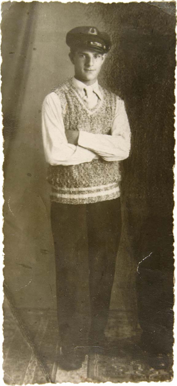 Portrait of a standing young man in a sailor's cap and a hand-knit sweater. He has a friendly look on his face and a delicate build.