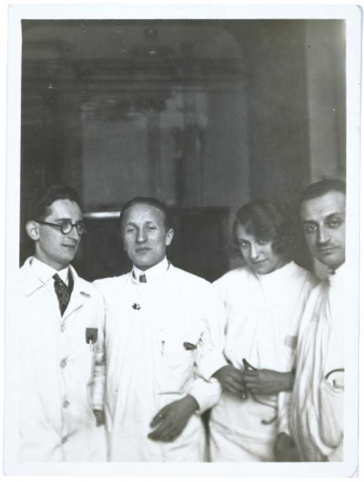 Black-and-white photograph. Erich Simenauer is the second from the left in a group of four. Standing to his right is a woman with a coy expression. Everyone is dressed in white doctor's coats. None of the three others have been identified.