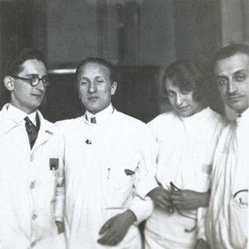 Schwarz-Weiß-Foto: Erich Simenauer steht als zweiter von links in einer Gruppe von vier Personen, rechts neben ihm steht eine Frau, die kess in die Kamera schaut, alle tragen weiße Kittel. Keiner der anderen Abgebildeten ist namentlich bekannt.